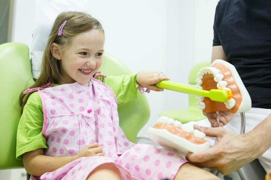 Девочка учится правильно чистить зубы